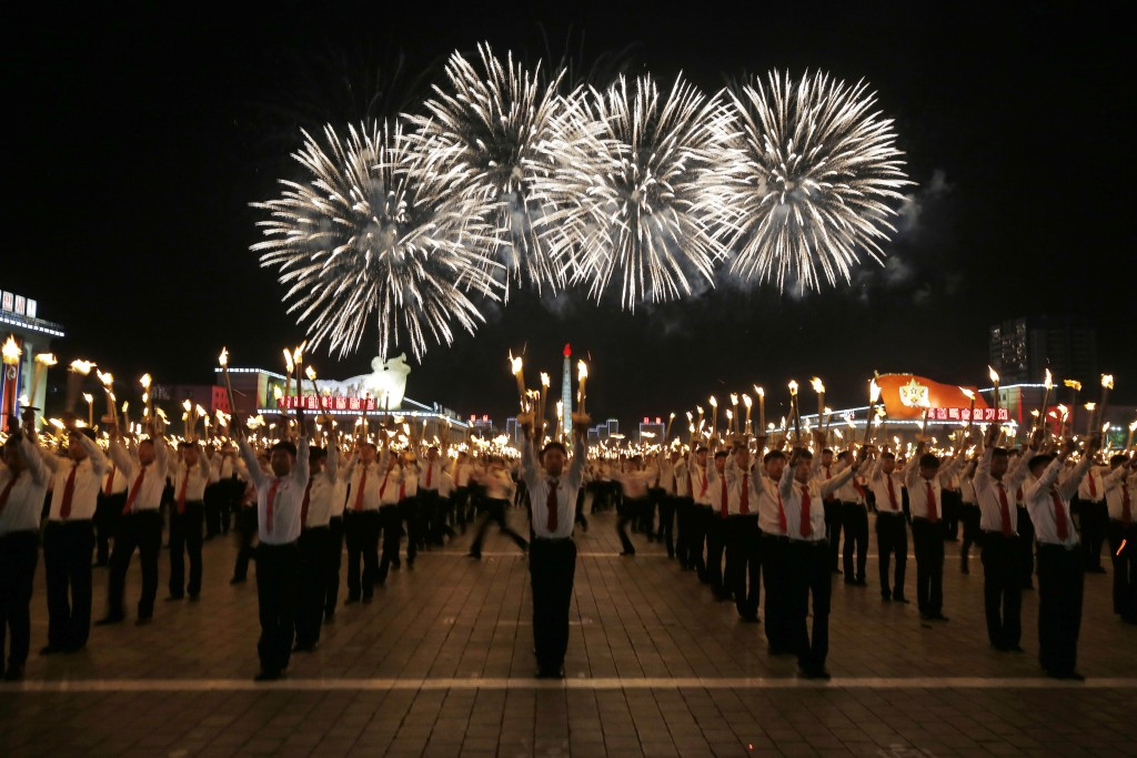 North Korean youths holding torches march during the torch light march at the Kim Il Sung Square in conjunction with the 70th anniversary of North Kor