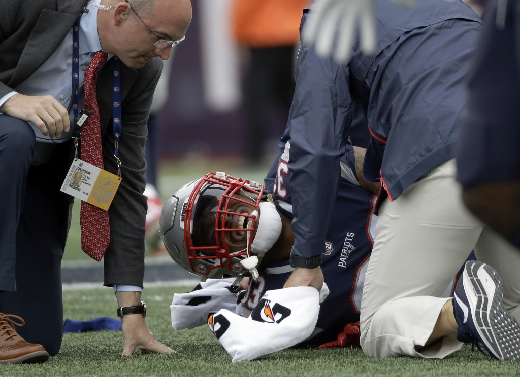 New England Patriots running back Jeremy Hill receives attention on the field after an injury during the second half of an NFL football game against t
