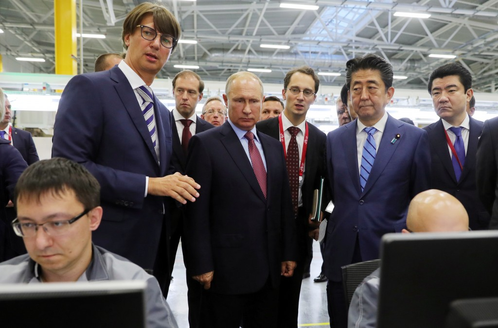 Japanese Prime Minister Shinzo Abe, second right, and Russian President Vladimir Putin, center, visit the Mazda Sollers Manufacturing Rus auto plant a