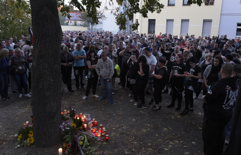 People gather at the site of a deadly brawl in Koethen, 90 miles southwest of the German capital Berlin, Sunday, Sept. 9, 2018, after police has arres