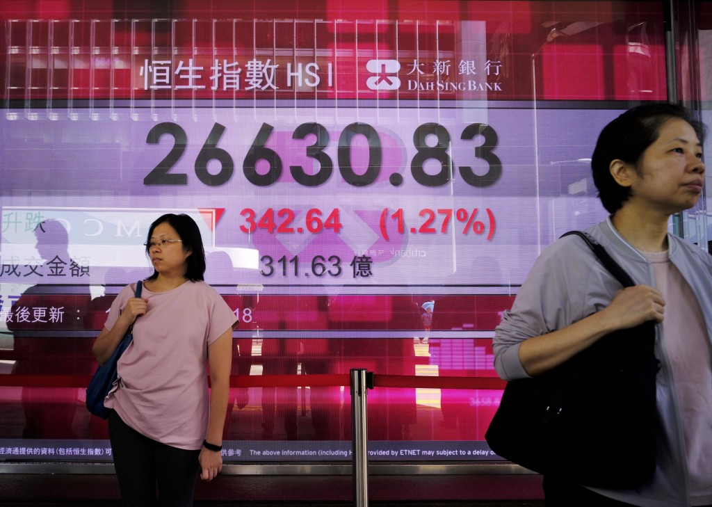 People walk past an electronic board showing Hong Kong share index outside a local bank in Hong Kong, Monday, Sept. 10, 2018. Asian shares are mixed a