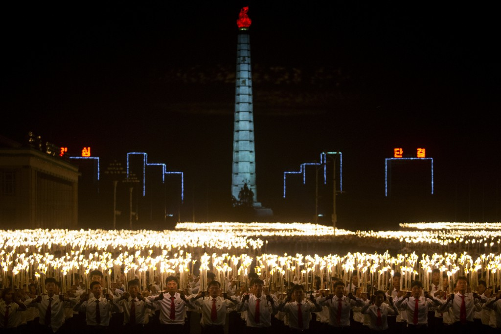 North Korean students take part in a torch light march held in conjunction with the 70th anniversary of North Korea's founding day celebrations in Pyo