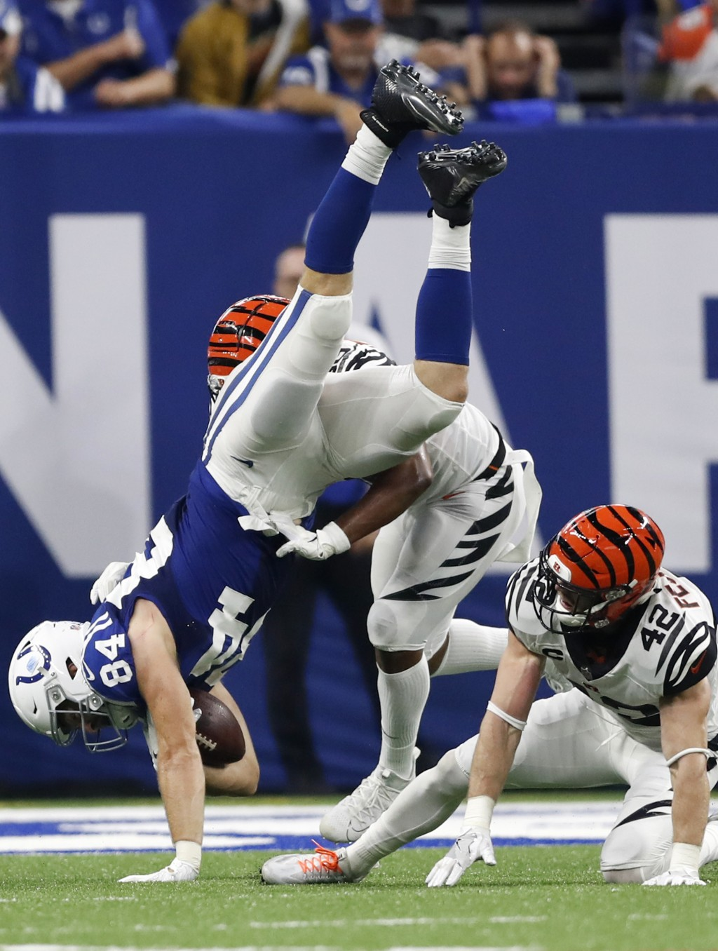 Indianapolis Colts tight end Jack Doyle (84) flips as he is hit by Cincinnati Bengals safety Clayton Fejedelem (42) and linebacker Hardy Nickerson dur
