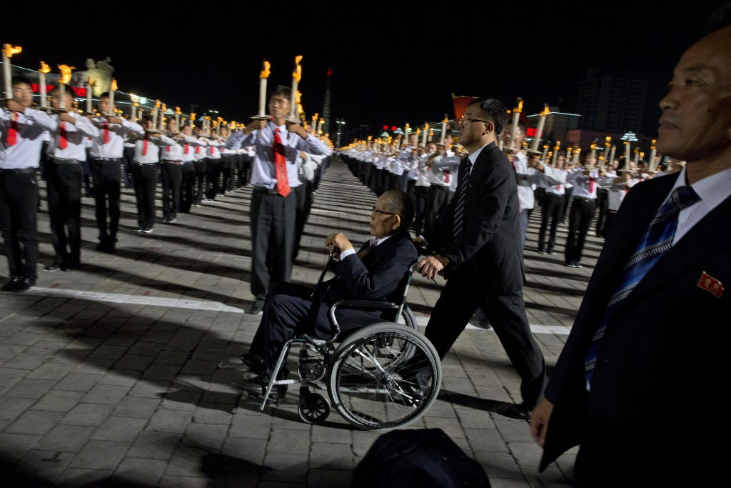 An elderly man is pushed past North Korean students taking part in a torch light march held in conjunction with the 70th anniversary of North Korea's
