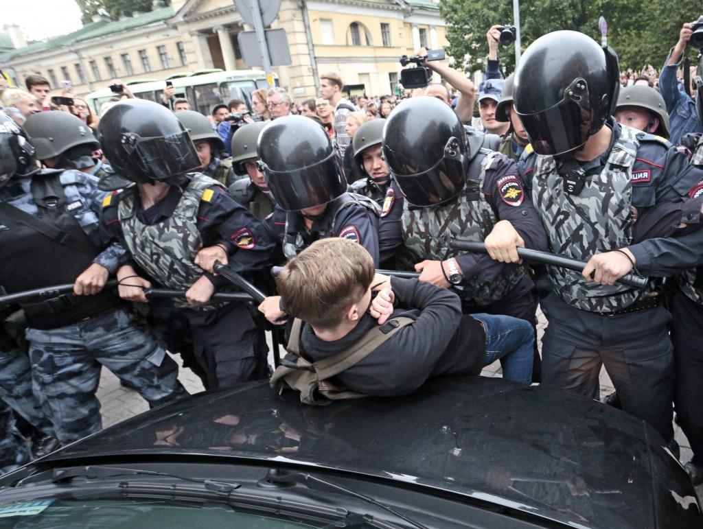 Russian police officers push a teenager during a rally protesting retirement age hikes in St. Petersburg, Russia, Sunday, Sept. 9, 2018. A government