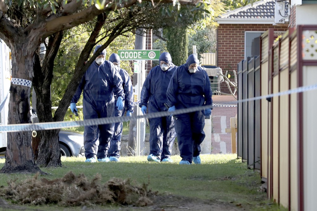 In this Sunday, Sept. 9, 2018 photo, forensic police officers inspect a property in suburban Perth, Australia. Three children, their mother and grandm