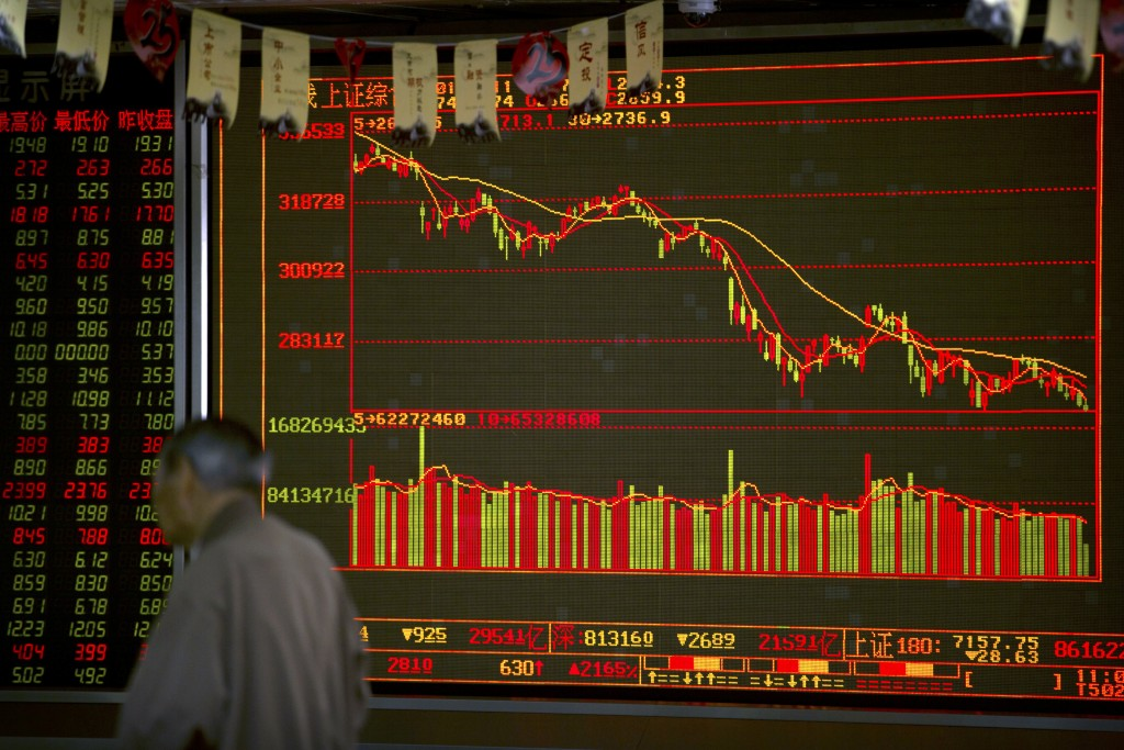 A Chinese investor walks past an electronic display at a brokerage house in Beijing, Tuesday, Sept. 11, 2018. Asian stocks were mixed Tuesday after Wa