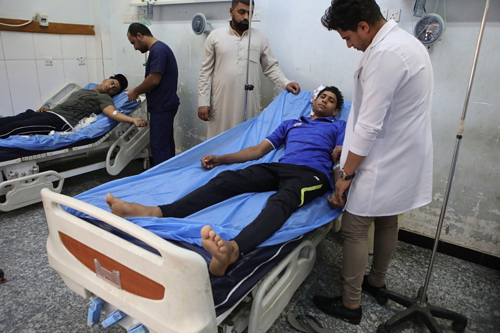 In this Sunday, Sept. 9, 2018 photo, injured protesters receive treatment at a hospital in Basra, Iraq. With brackish water pouring from the taps, fai