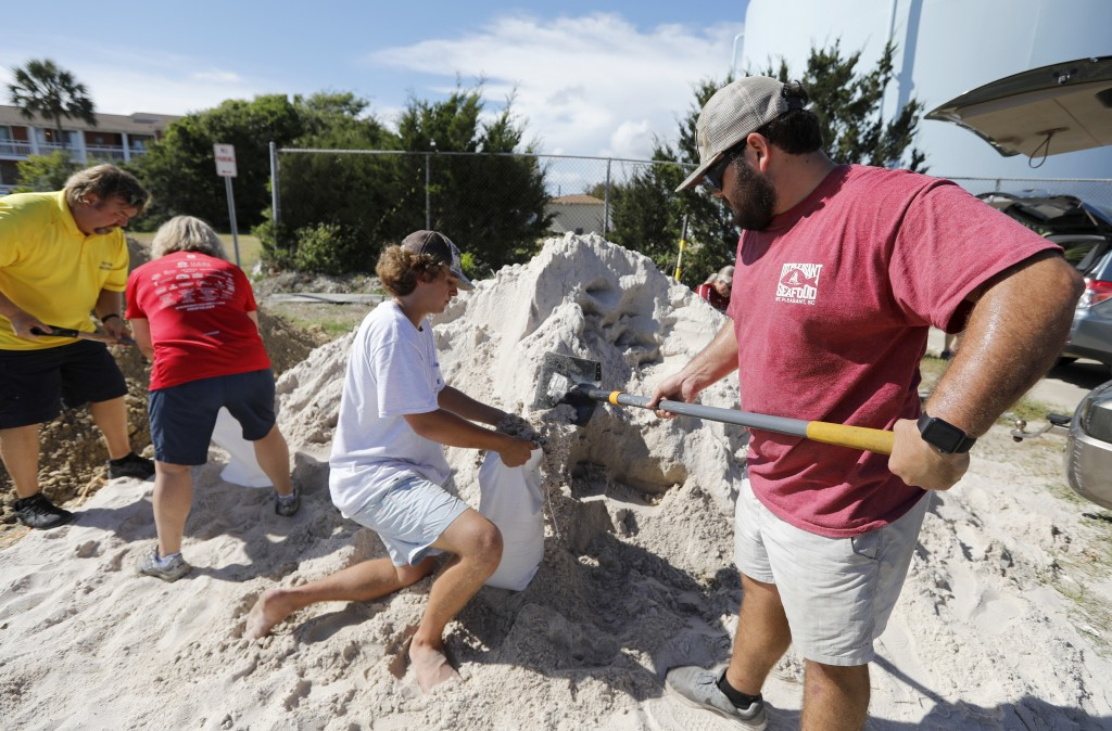 Walker Townsend, at right, from the Isle of Palms, S.C., fills a sand bag while Dalton Trout, in center, holds the bag at the Isle of Palms municipal