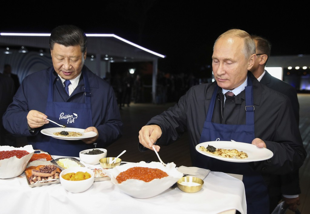 Chinese President Xi Jinping, left, and Russian President Vladimir Putin select food, as they visit an exhibition during the Eastern Economic Forum in