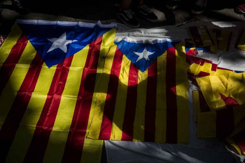 A shadow of a man is cast over Catalan independence flags for sale, during the Catalan National Day in downtown Barcelona, Spain, Tuesday, Sept. 11, 2