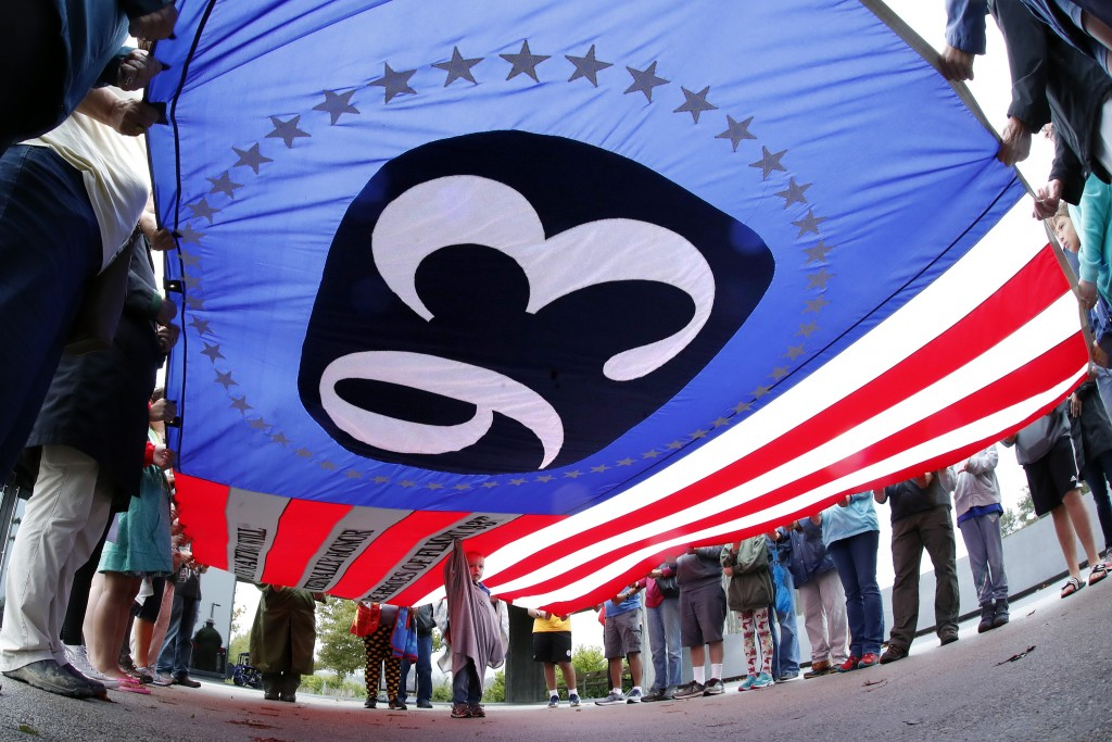Visitors to the Flight 93 National Memorial in Shanksville, Pa., hold a giant Flight 93 flag during a moment of remembrance Monday, Sept. 10, 2018, as...