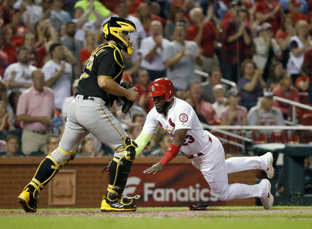 St. Louis Cardinals' Marcell Ozuna, right, scores past Pittsburgh Pirates catcher Francisco Cervelli during the fourth inning of a baseball game Monda