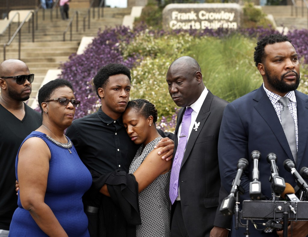 Brandt Jean, center left, brother of shooting victim Botham Jean, hugs his sister Allisa Charles-Findley, during a news conference outside the Frank C