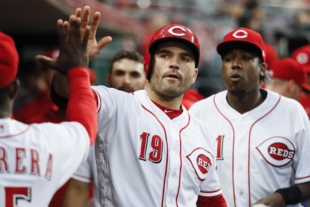 Cincinnati Reds' Joey Votto celebrates in the dugout after scoring off an RBI single by Scooter Gennett off Los Angeles Dodgers starting pitcher Alex