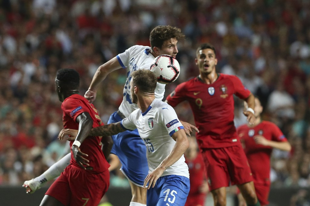 Italy's Mattia Caldara, centre, jumps for as header during the UEFA Nations League soccer match between Portugal and Italy at the Luz stadium in Lisbo