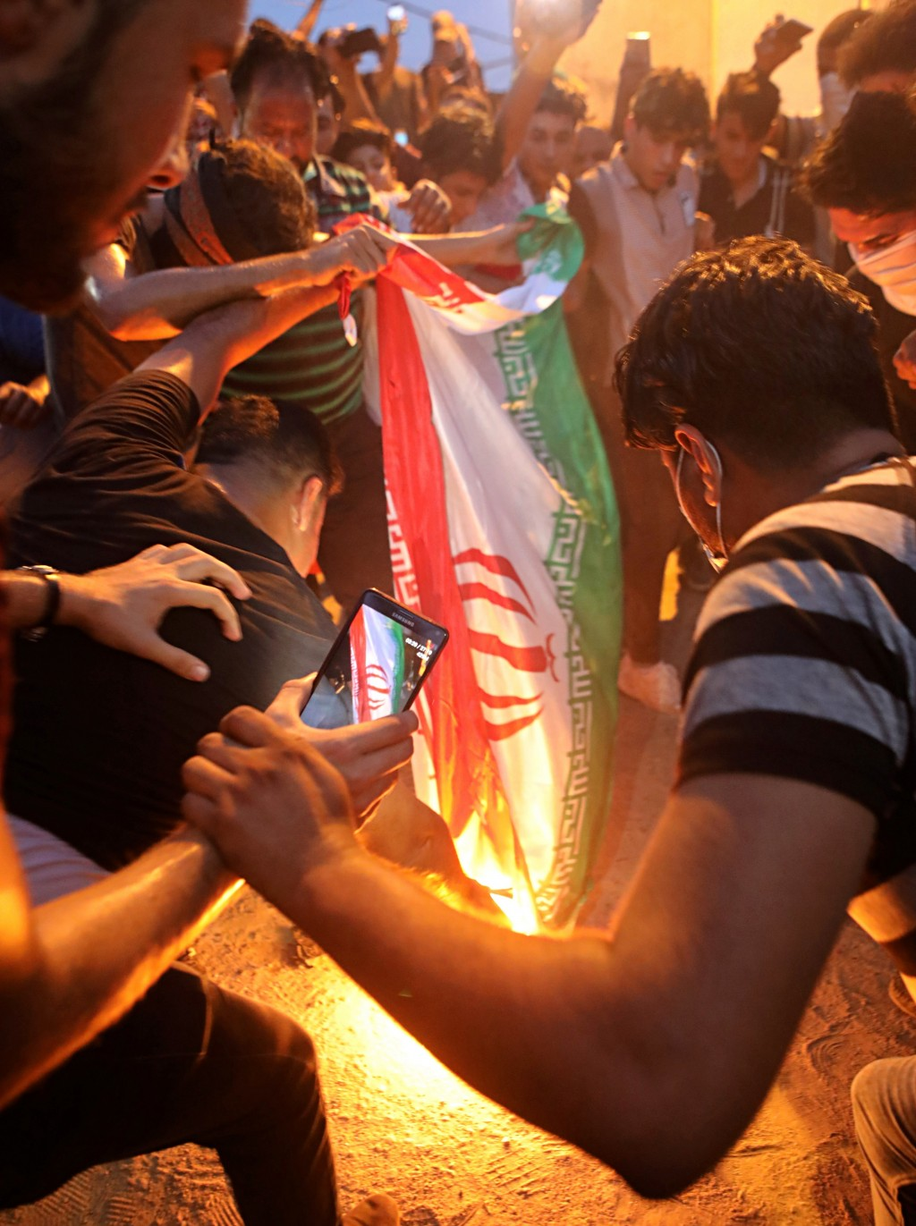 FILE - In this Friday, Sept. 7, 2018 file photo, protesters burn an Iranian flag after storming and burning the Iranian consulate building in Basra, I