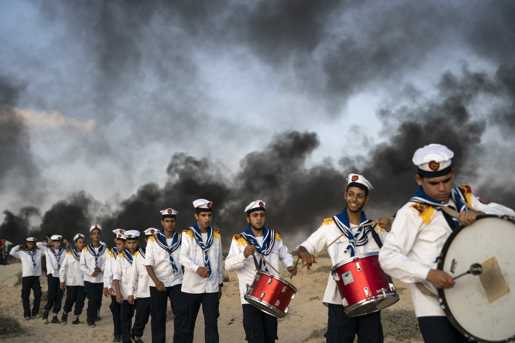 Palestinian boy scouts march during a protest on the beach near the border with Israel in Beit Lahiya, northern Gaza Strip, Monday, Sept. 10, 2018. Th