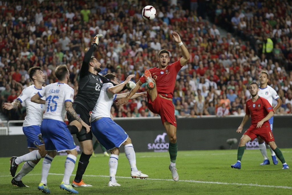 Portugal's Andre Silva, centre, challenges Italy goalkeeper Gianluigi Donnarumma and three Italian defenders during the UEFA Nations League soccer mat