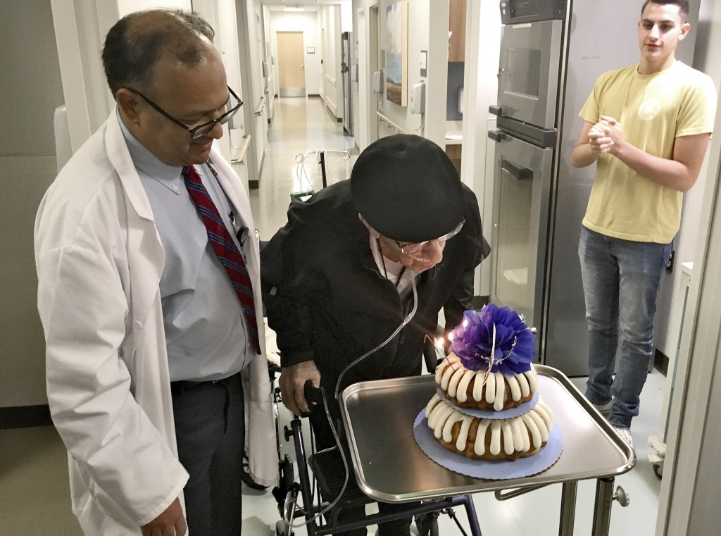 Dr. Rajneesh Nath, left, watches the Rev. John Sabbagh blow out candles on his cake for his one-year transplant anniversary as Sabbagh's grandson John