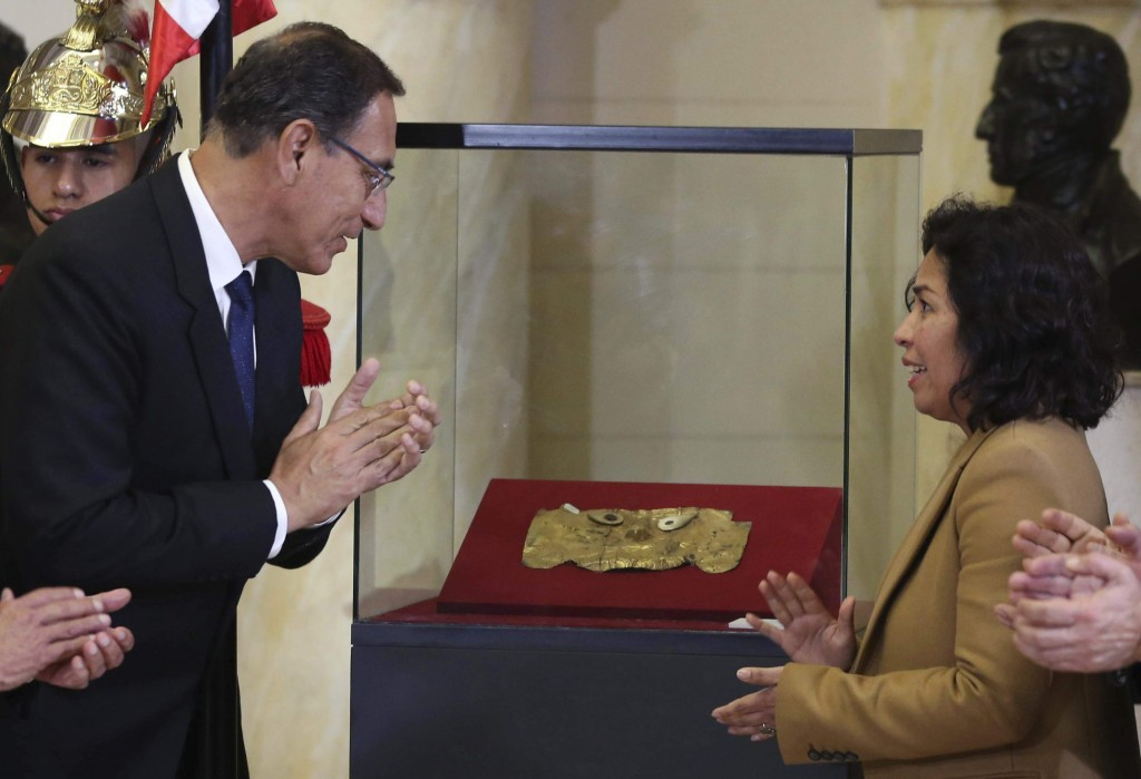 Peru's President Martin Vizcarra, left, and Culture Minister Patricia Balbuena, celebrate the return of the pre-Columbian gold funerary Sican mask, th
