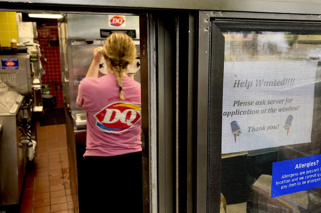 "FILE - In this Sunday, Aug. 19, 2018, file photo a woman prepares a cup of ice cream behind a ""Help Wanted"" sign at a Dairy Queen fast food restaurant"