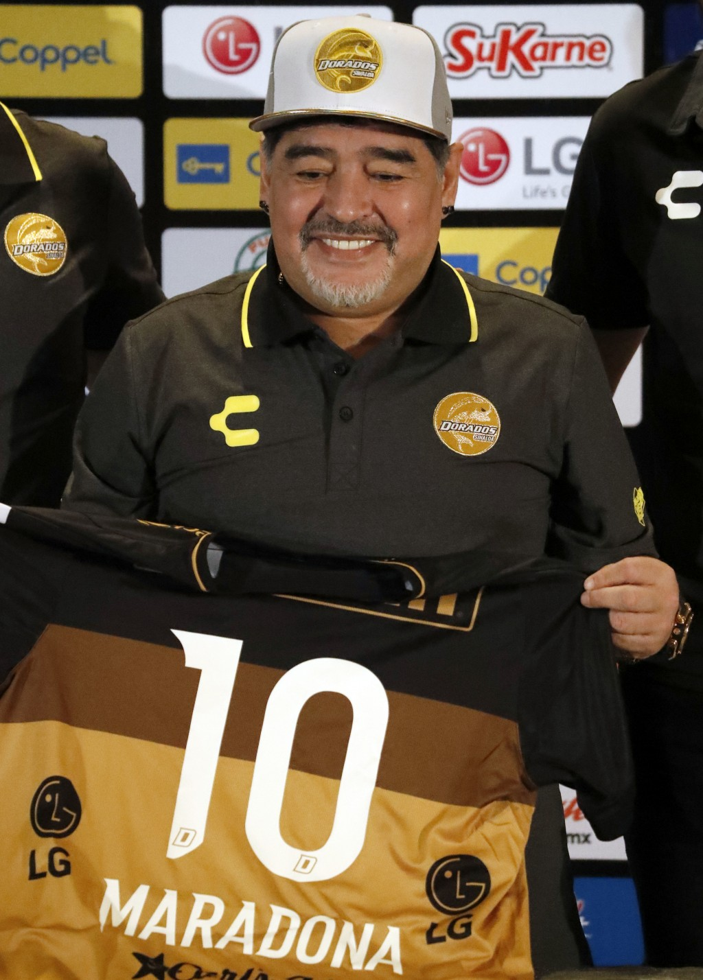 Former soccer great Diego Maradona, shows his team jersey during a press conference where he was presented as the new manager of the Dorados of Sinalo