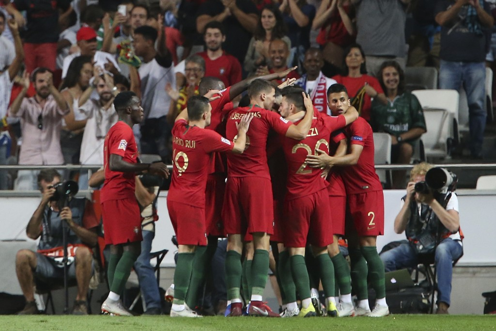 Portugal players celebrate after Andre Silva scored the opening goal during the UEFA Nations League soccer match between Portugal and Italy at the Luz