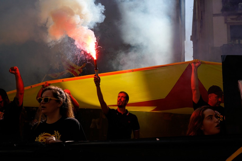 "Demonstrators, some of them holding flares, march carrying ""esteladas"" or independence flags during the Catalan National Day in Barcelona, Spain, Tues"