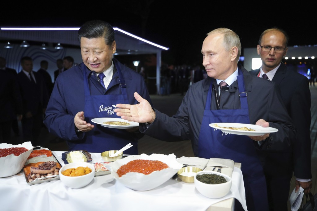 Russian President Vladimir Putin, right, gestures as he and Chinese President Xi Jinping select food, as they visit an exhibition during the Eastern E