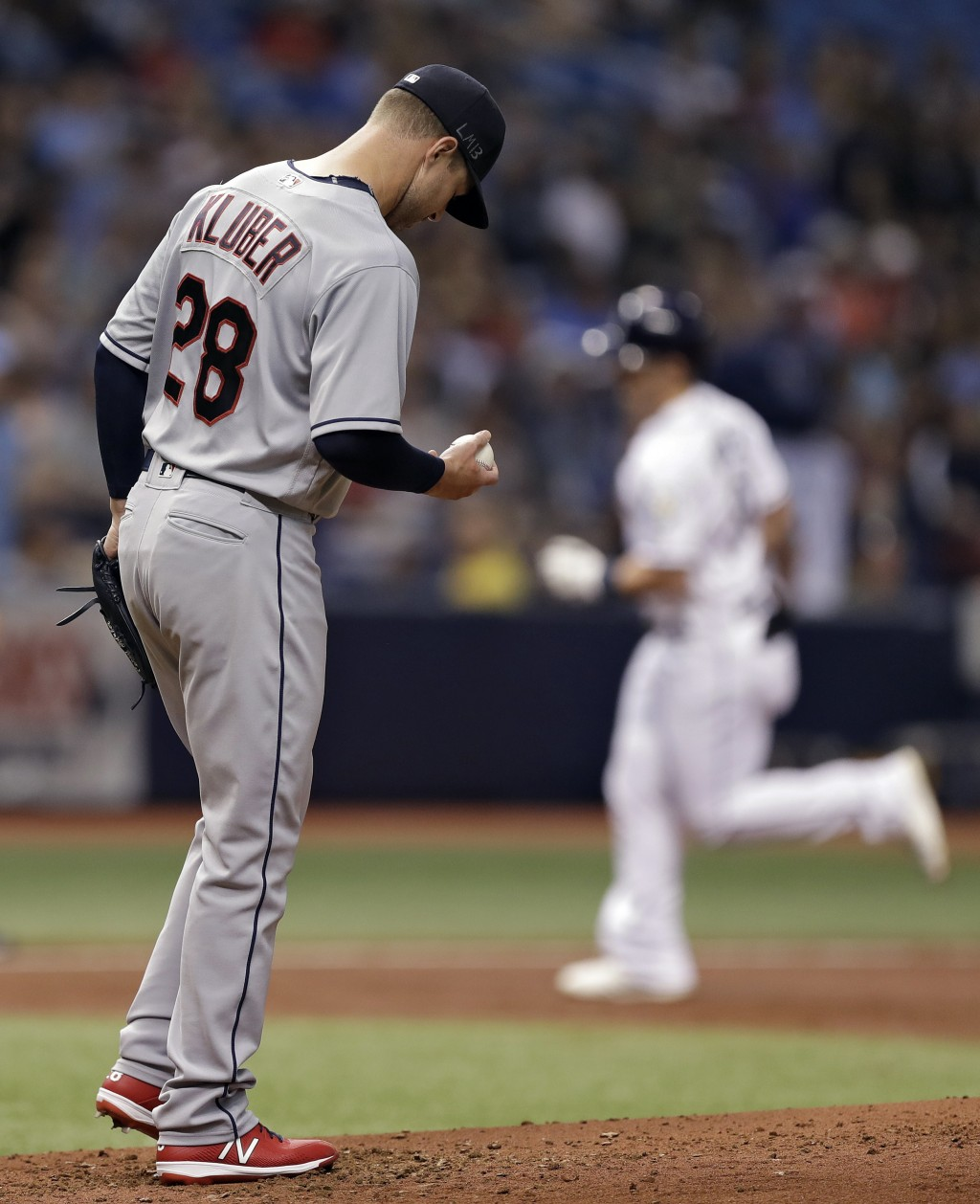 Cleveland Indians pitcher Corey Kluber reacts as Tampa Bay Rays' Jake Bauers, right, runs around the bases after Bauers hit a two-run home run during