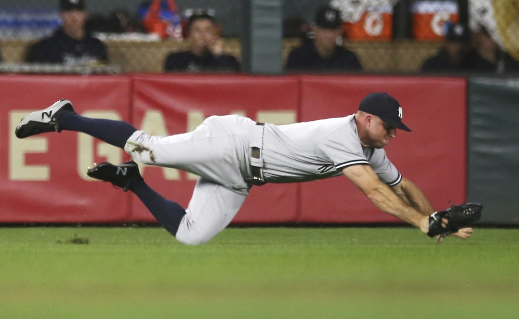 New York Yankees left fielder Brett Gardner dives for the ball hit by Minnesota Twins' Johnny Field in the second inning of a baseball game Monday, Se