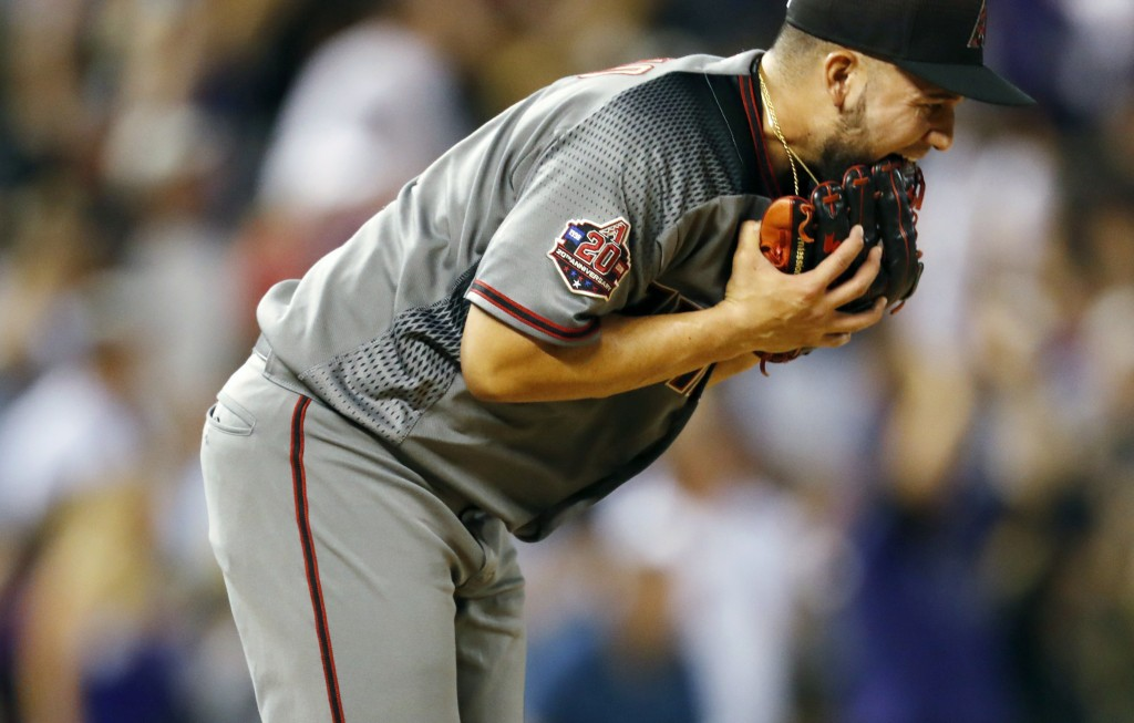 Arizona Diamondbacks relief pitcher Silvino Bracho bites his glove after giving up a three-run home run to Colorado Rockies' Trevor Story in the fifth