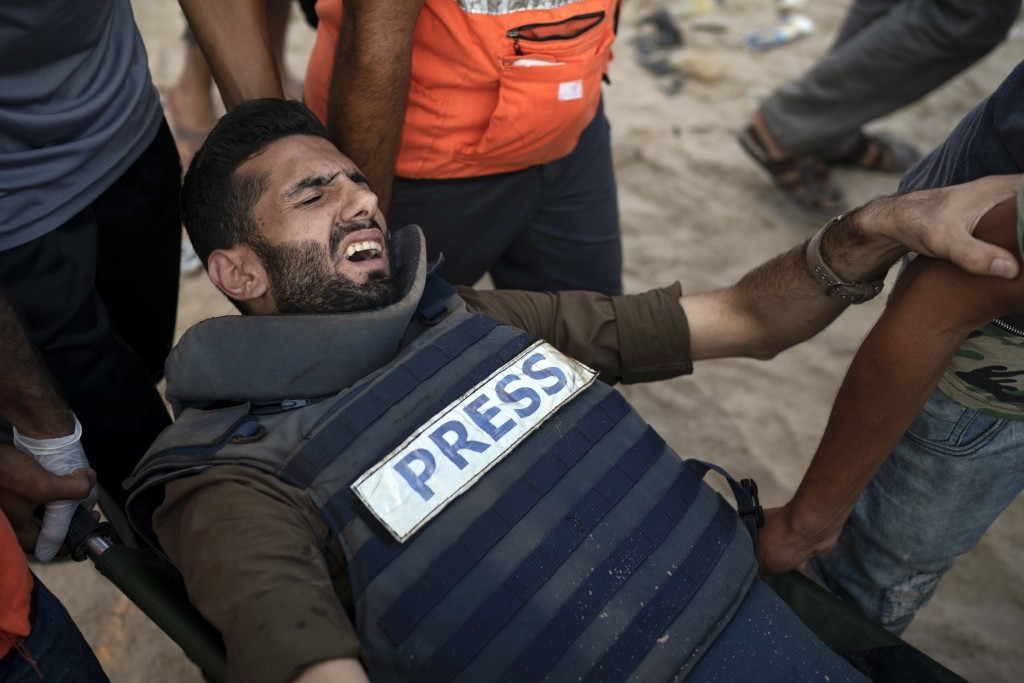 Palestinian cameraman Atia Hijazi is carried to an ambulance after being shot by Israeli soldiers during a protest on the beach near the border with I
