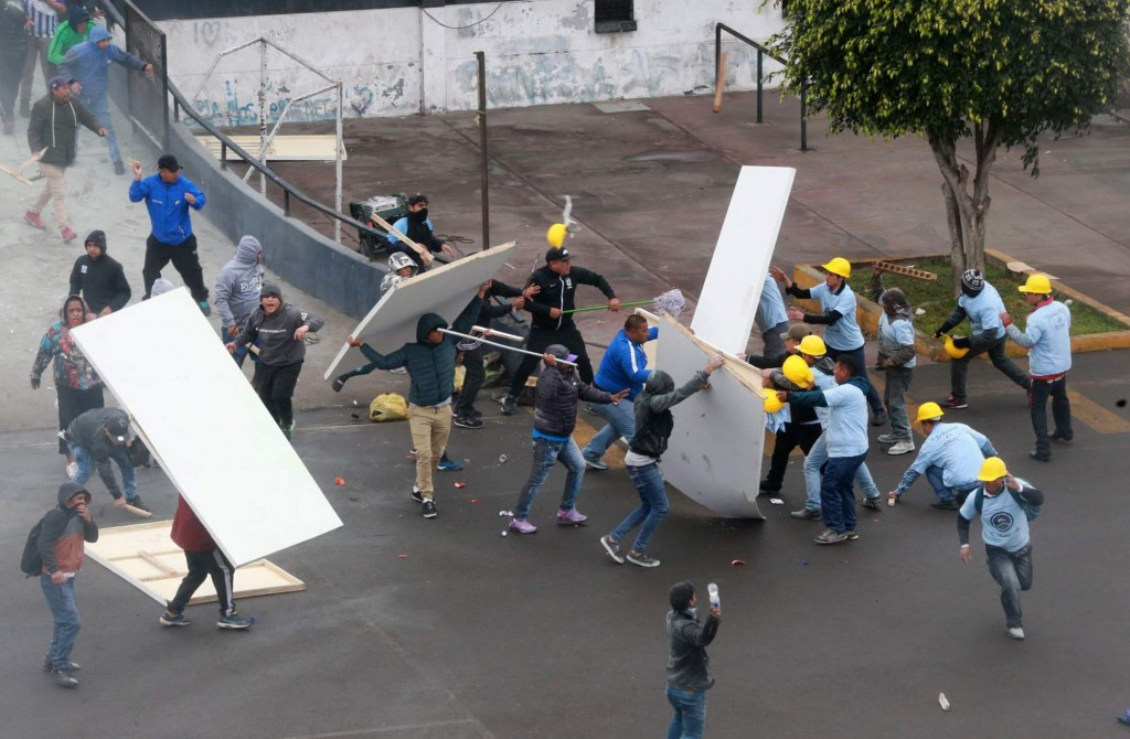 In this photo provided by the Andina government news agency, Alianza Lima club soccer fans, left, fight with members of an evangelical church, yellow