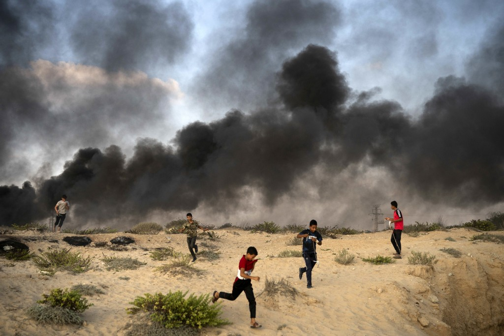 Young Palestinian protesters run from tear gas fired by Israeli soldiers during a protest on the beach near the border with Israel in Beit Lahiya, nor