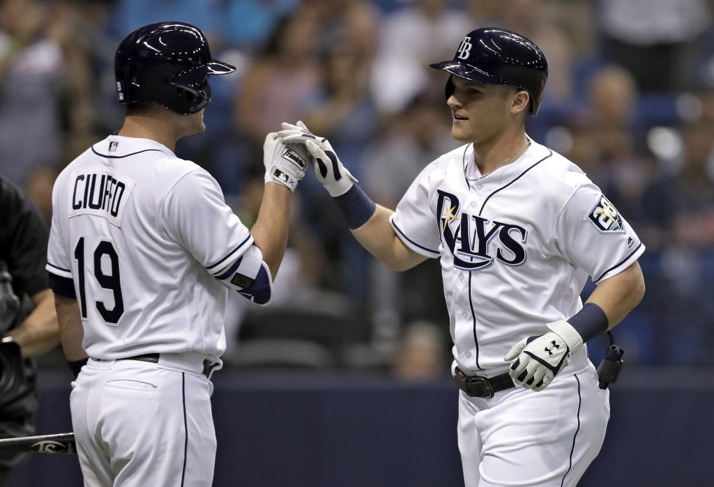 Tampa Bay Rays' Jake Bauers, right, high fives on-deck batter Nicholas Ciuffo after Bauers hit a two-run home run off Cleveland Indians pitcher Corey