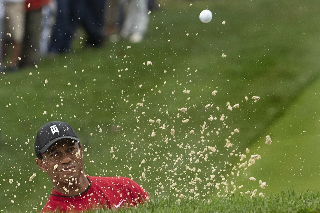 Tiger Woods plays a shot from the bunker on the 14th hole during the BMW Championship golf tournament at the Aronimink Golf Club, Monday, Sept. 10, 20