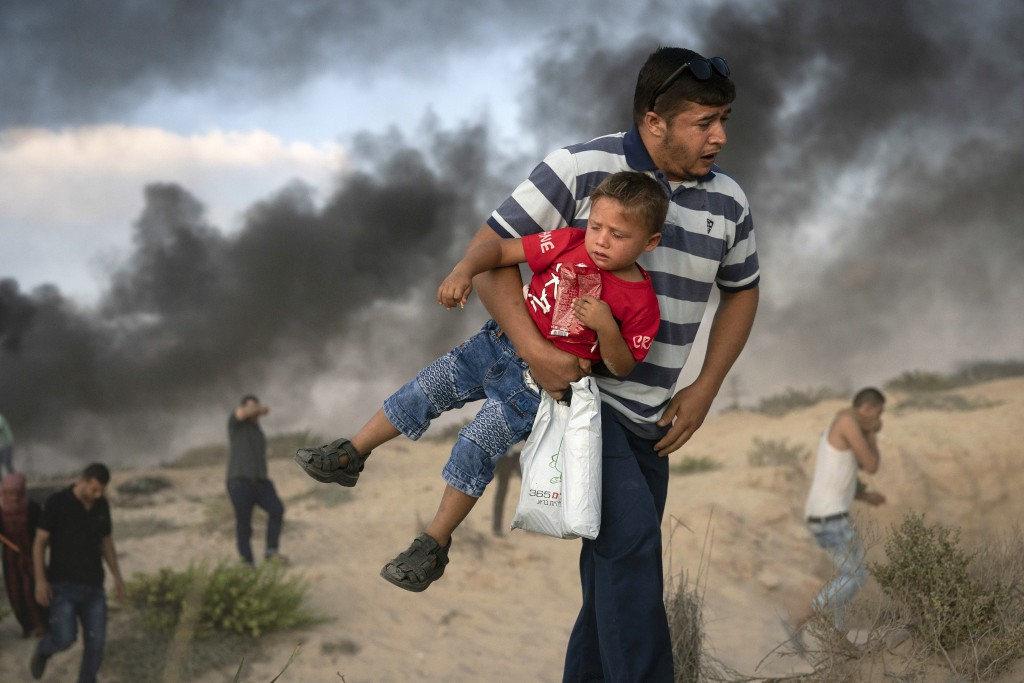 A Palestinian protester carries a boy as he runs from tear gas fired by Israeli soldiers during a protest on the beach near the border with Israel in
