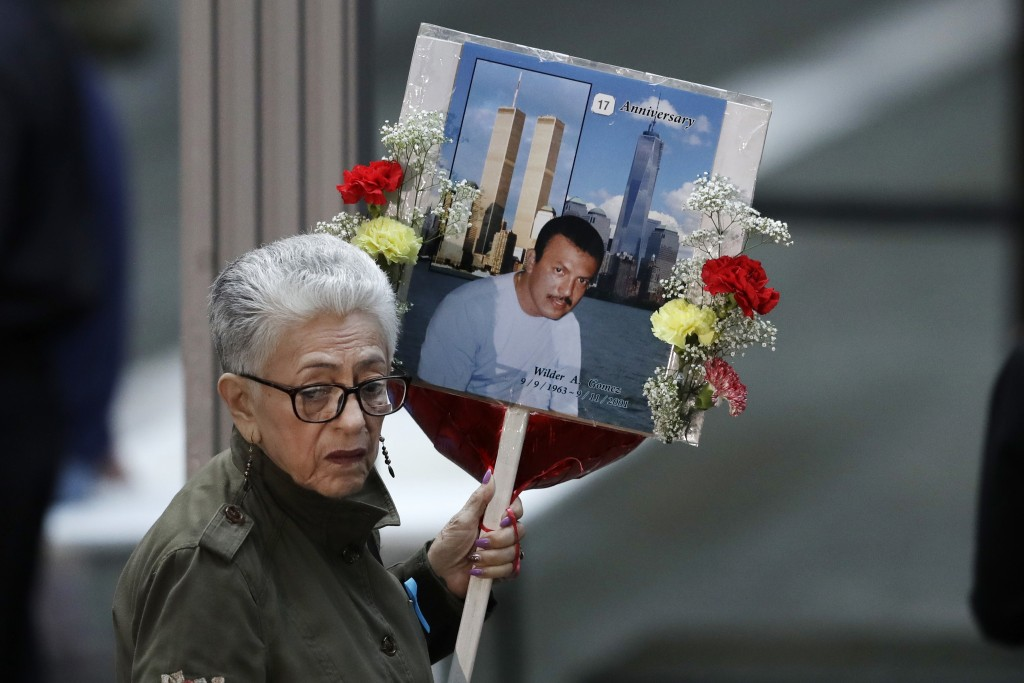 A woman arrives with a sign bearing photo memories for Wilder Gomez at the 17th anniversary of the terrorist attacks on the United States, Tuesday, Se