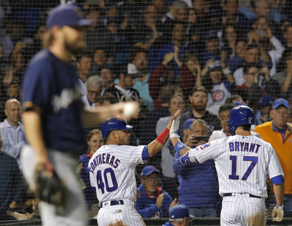Chicago Cubs' Willson Contreras, center, celebrates scoring a run with Chicago Cubs' Kris Bryant, right, against Milwaukee Brewers' Wade Miley during