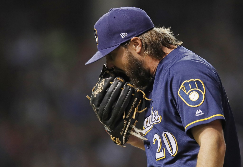 Milwaukee Brewers' Wade Miley yells into his glove as he walks off the field at the end of the first inning of a baseball game Monday, Sept. 10, 2018,