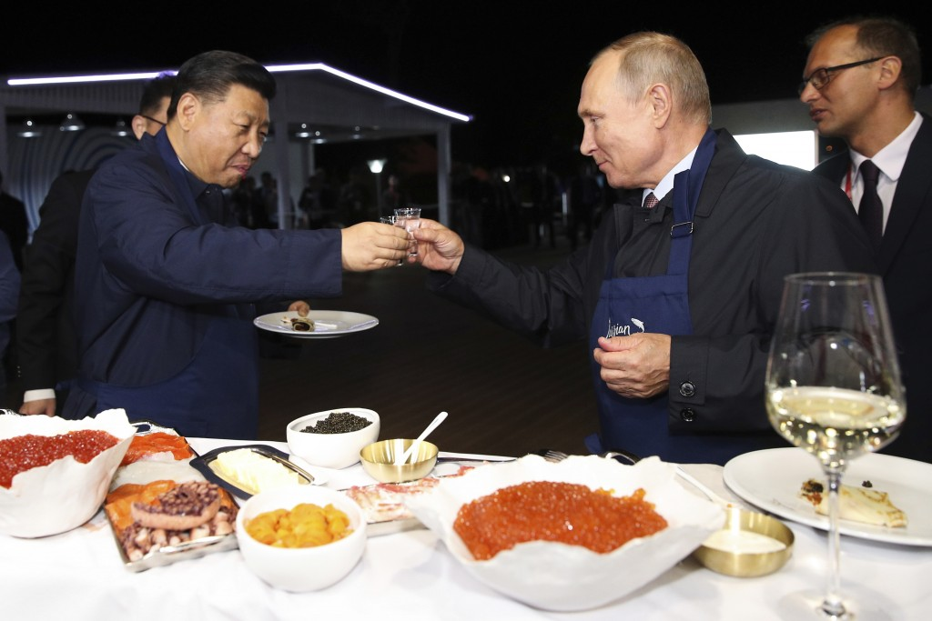 Chinese President Xi Jinping, left, and Russian President Vladimir Putin toast as they taste a food, during a visit to an exhibition during the Easter