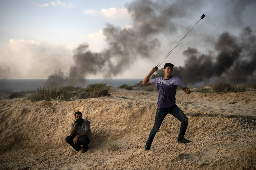 A young Palestinian protester hurls stones during a protest on the beach near the border with Israel in Beit Lahiya, northern Gaza Strip, Monday, Sept