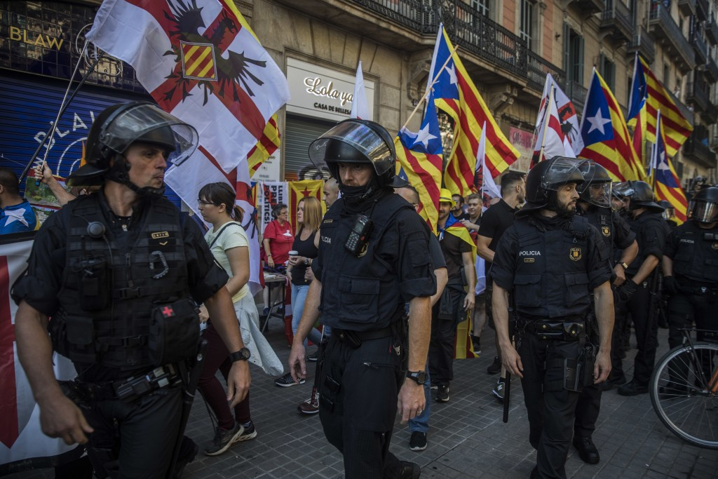 Members of a ultra-right-wing movement called 'Catalan Identitarian Movement' walk guarded by the police during celebrations of the Catalonia's region