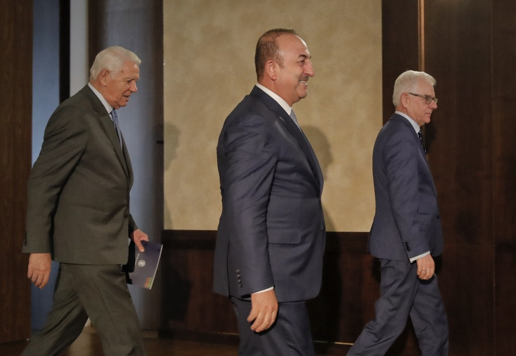 Turkey's Foreign Minister Mevlut Cavusoglu, center, walks with Polish Foreign Minister Jacek Czaputowicz, right, and Romanian Foreign Minister Teodor