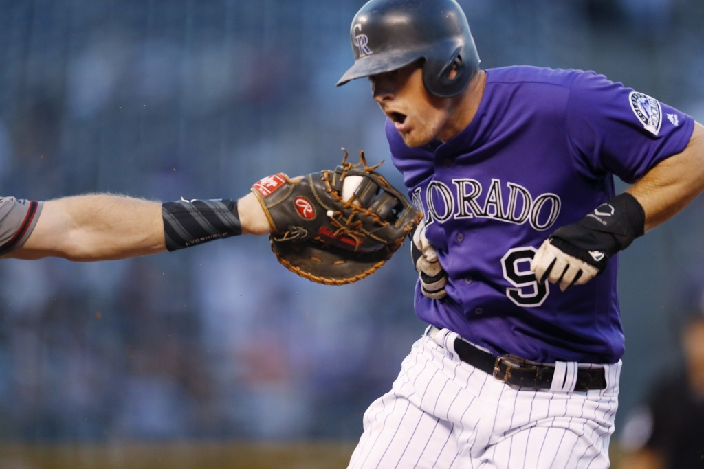 Arizona Diamondbacks first baseman Paul Goldschmidt, left, reaches out to put the tag on Colorado Rockies' DJ LeMahieu after he was caught in a rundow