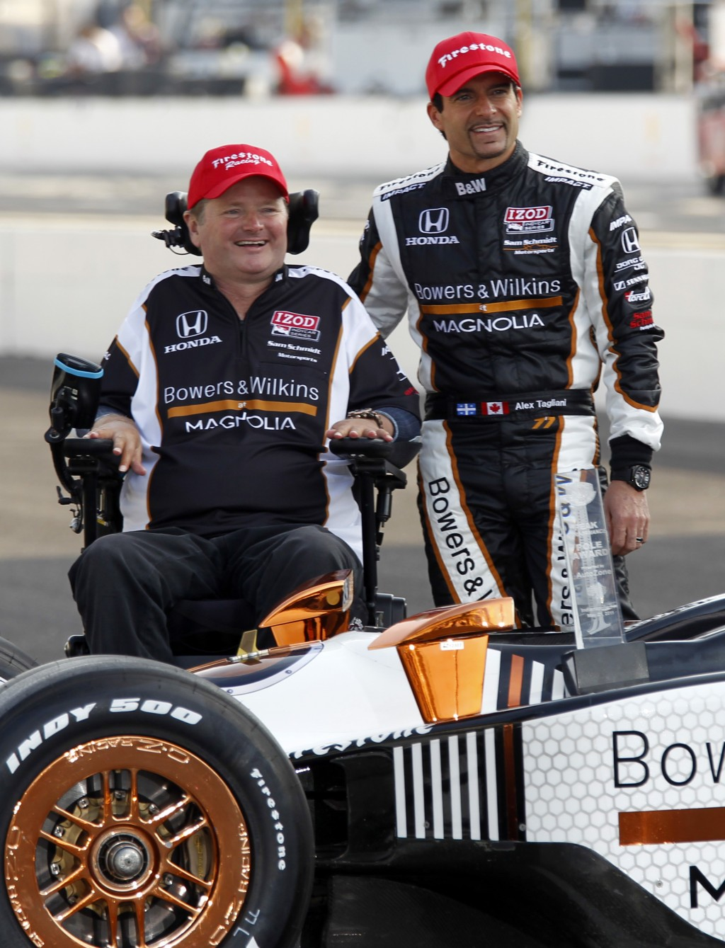 FILE - In this May 22, 2011 file photo, pole sitter Alex Tagliani, right, of Canada, poses with car owner Sam Schmidt on the start/finish line at the