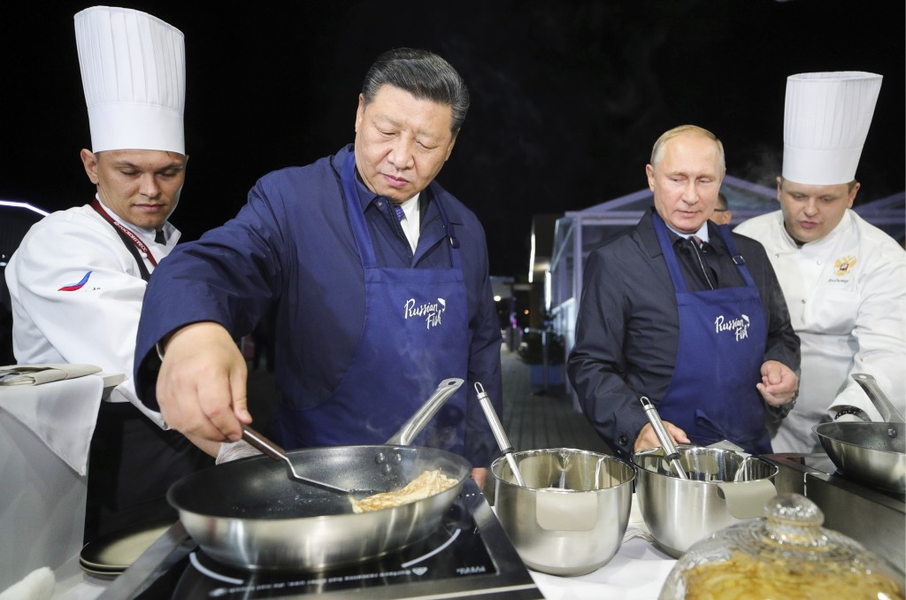 Chinese President Xi Jinping, second left, and Russian President Vladimir Putin, second right, prepare food, as they visit an exhibition during the Ea