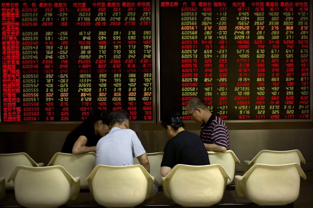 Chinese investors play cards near an electronic display showing stock prices at a brokerage house in Beijing, Tuesday, Sept. 11, 2018. Asian stocks we